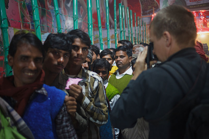 Maciej Dakowicz photographs men in a queue to a theatre staging dance shows at Sonepur Mela, India.
